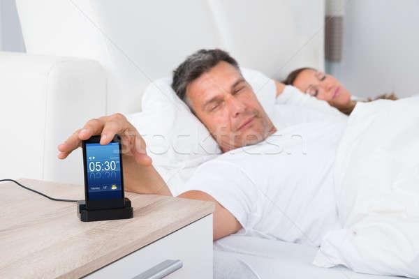 Homem cama despertador celular tela mulher Foto stock © AndreyPopov