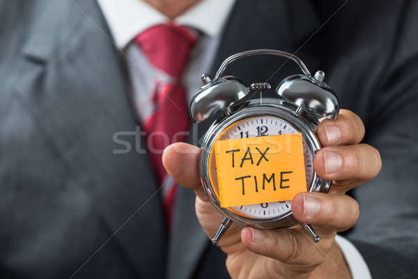 Businessman Holding Alarm Clock With Tax Time Note Stock photo © AndreyPopov