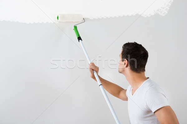 Man Painting Wall With Paint Roller Stock photo © AndreyPopov