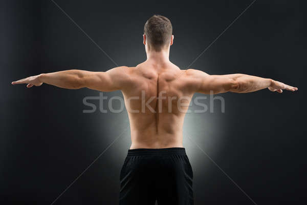 Rear View Of Muscular Man Standing Arms Outstretched Stock photo © AndreyPopov