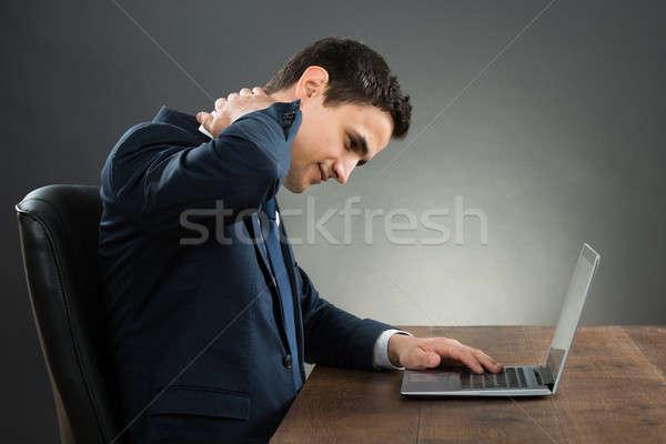Empresario sufrimiento dolor de cuello usando la computadora portátil escritorio jóvenes Foto stock © AndreyPopov
