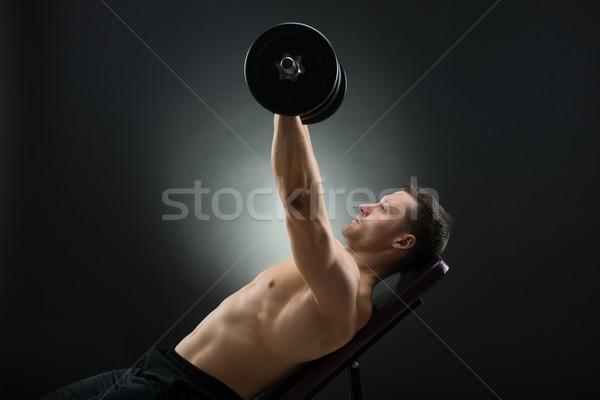 Határozott férfi emel súlyzók szék felnőtt Stock fotó © AndreyPopov