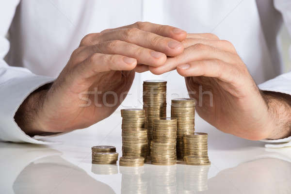 Businessman Protecting Stacked Coins At Desk Stock photo © AndreyPopov