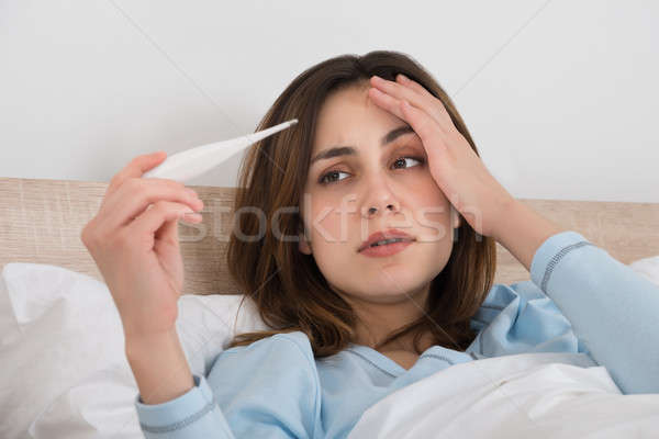Stock photo: Sick Woman Holding Thermometer