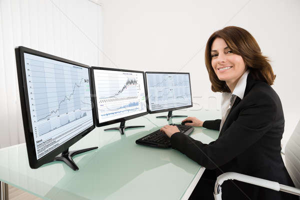 Female Stock Market Broker Working On Multiple Computers Stock photo © AndreyPopov