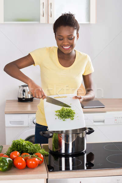 Woman Putting Chopped Vegetables In Utensil Stock photo © AndreyPopov