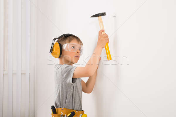Boy Hammering Nail In Wall Stock photo © AndreyPopov