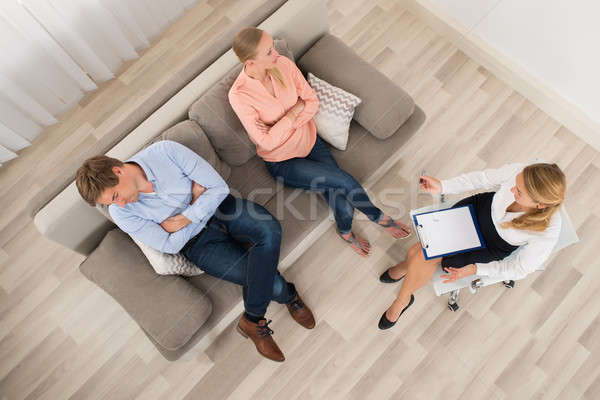 Unhappy Couple Sitting With Psychologist At Home Stock photo © AndreyPopov