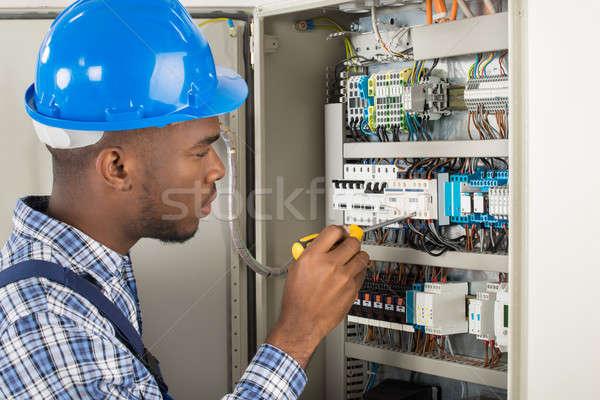 Electrician Examining Fusebox With Screwdriver Stock photo © AndreyPopov