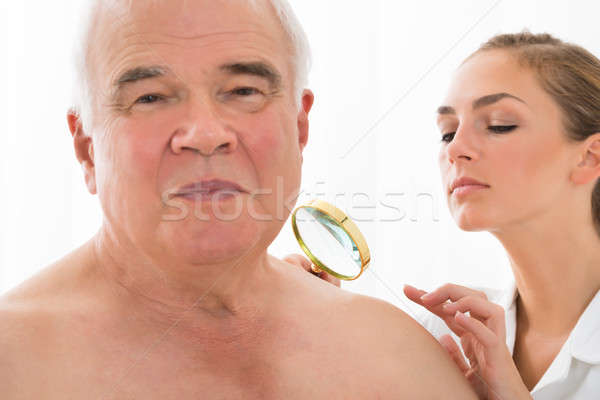 Doctor Examining Skin Of Patient With Magnifying Glass Stock photo © AndreyPopov