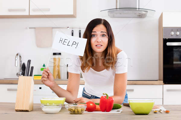 Woman Holding Help Flag In Kitchen Stock photo © AndreyPopov