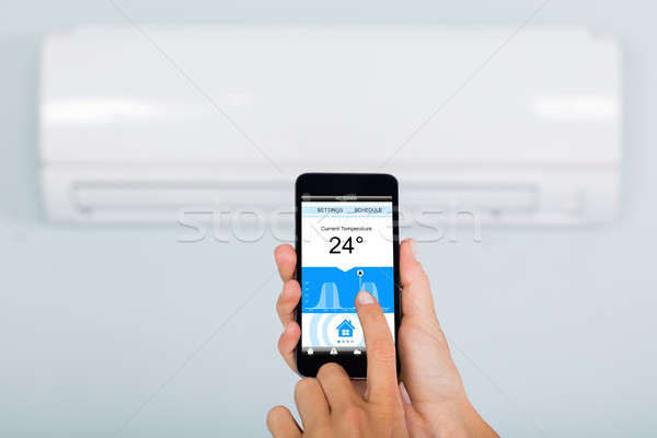 Stock photo: Woman Operating Air Conditioner Using Smartphone