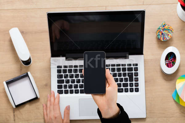 Businesswoman Using Laptop And Mobilephone Stock photo © AndreyPopov