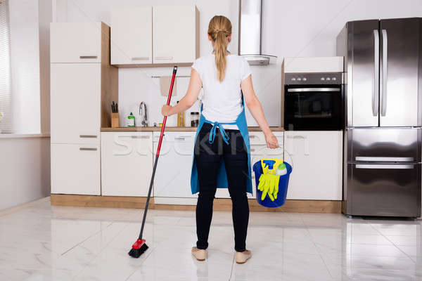 Housemaid With Cleaning Equipment Standing In Kitchen Stock photo © AndreyPopov