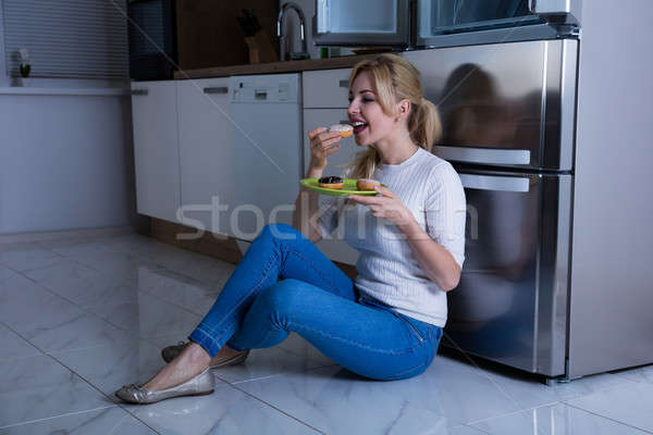 Woman Eating Sweet Food Near Refrigerator Stock photo © AndreyPopov