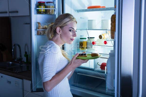Gyanús nő elvesz étel hűtőszekrény édes étel Stock fotó © AndreyPopov