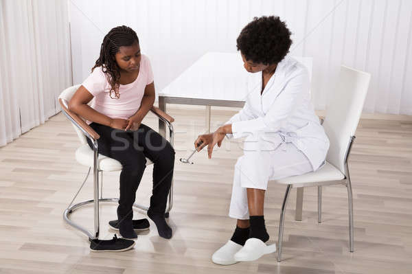 Doctor Checking Reflexes Of Knee Pain Stock photo © AndreyPopov