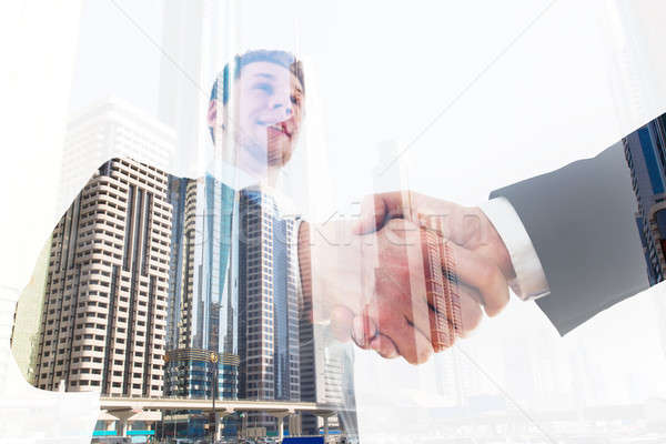 Businessman Shaking Hand With Coworker Over City Background Stock photo © AndreyPopov