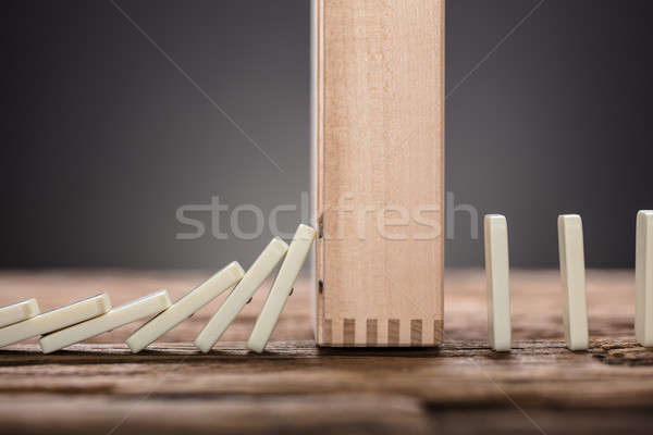 Wooden Block Amidst Falling And Upright Domino Pieces On Table Stock photo © AndreyPopov
