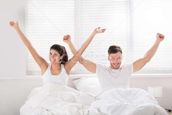 Gelukkig paar bed glimlachend arm Stockfoto © AndreyPopov