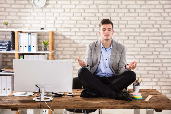 Businessman Meditating In Office Stock photo © AndreyPopov