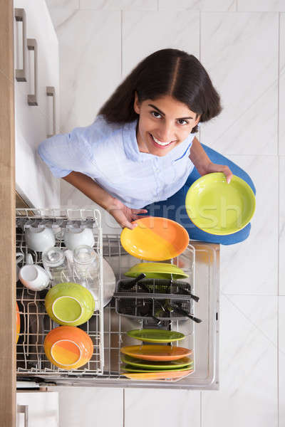 Young Woman Arranging Plates In Dishwasher Stock photo © AndreyPopov
