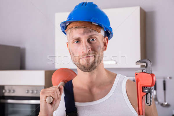 Young Plumber Holding Wrench And Plunger In Kitchen Stock photo © AndreyPopov