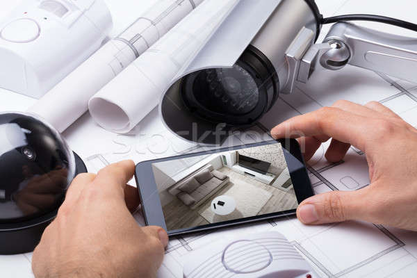 Person Hand Using Home Security System On Mobilephone Stock photo © AndreyPopov