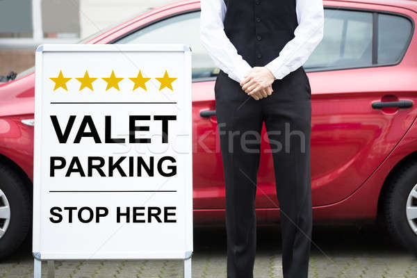 Young Male Valet Standing Near Valet Parking Sign Stock photo © AndreyPopov