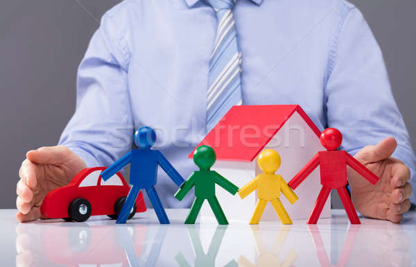 Businessperson Protecting Human Figures, House Model And Car Stock photo © AndreyPopov