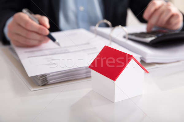 House Model In Front Of Businessperson Calculating Bill Stock photo © AndreyPopov