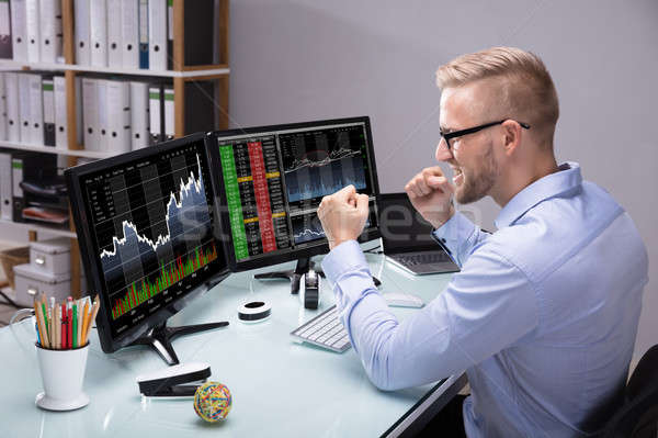 Excited Stock Market Broker Looking At Graph On Computer Stock photo © AndreyPopov