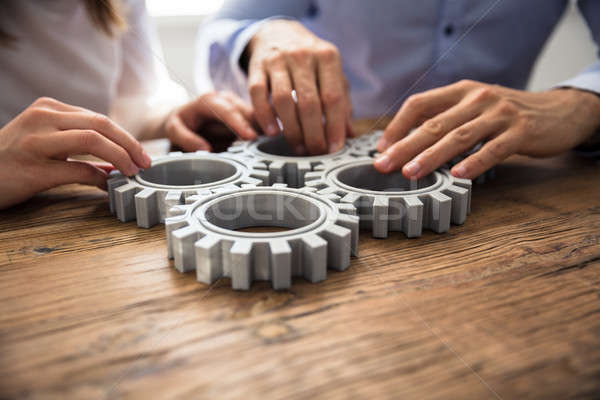 Stock photo: Two Businesspeople Joining Gears