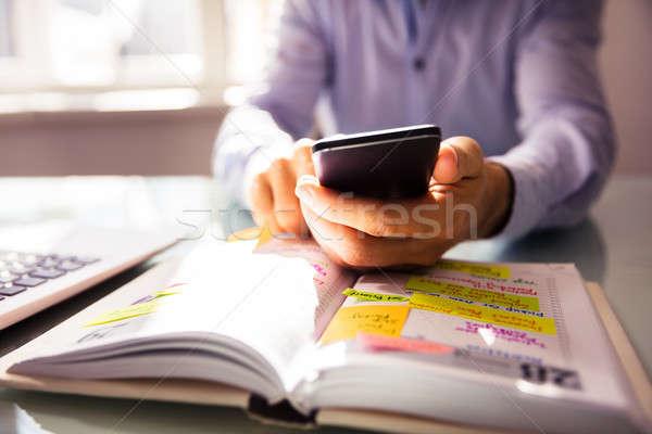 Empresário telefone móvel diário secretária trabalhar empresário Foto stock © AndreyPopov