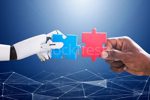 Robot And Human Hand Joining Jigsaw Stock photo © AndreyPopov