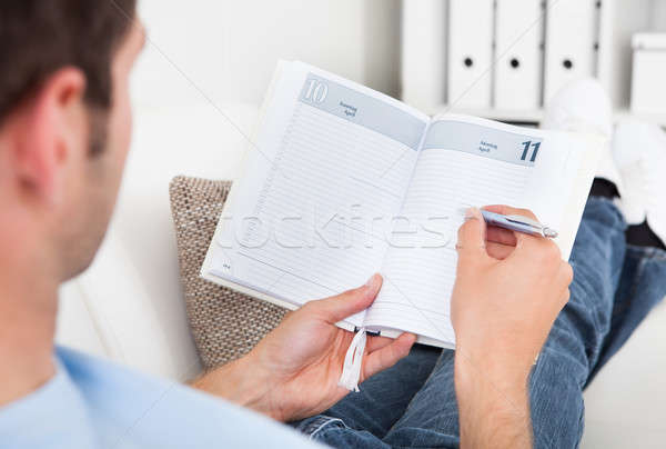 Man Writing In Diary Stock photo © AndreyPopov
