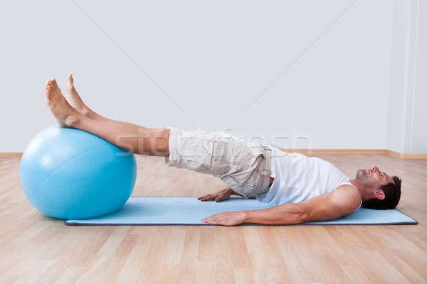 Young Man Exercising On A Pilates Ball Stock photo © AndreyPopov