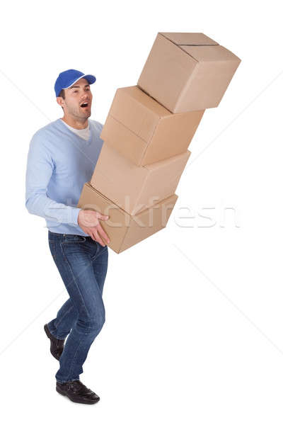 Stock photo: Young delivery man with falling boxes