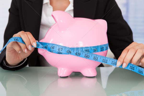 Stock photo: Businesswoman Measuring Piggybank At Desk