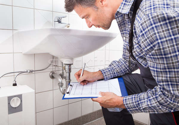 Plumber Writing On Clipboard Stock photo © AndreyPopov