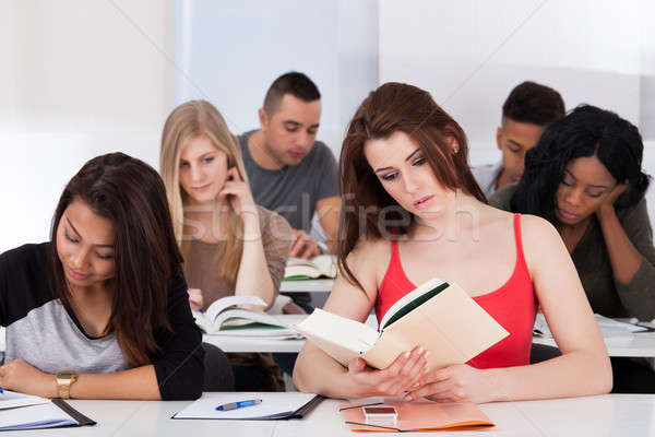 Stock photo: Beautiful college student reading book