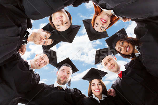Happy Multiethnic Graduates Forming Huddle Against Sky Stock photo © AndreyPopov