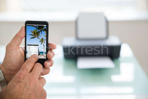 Stock photo: Person Using Cellphone For Printing Photo