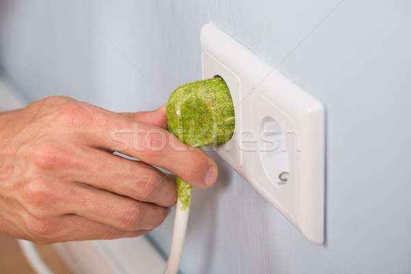 Closeup Of Hand With Electrical Plug And Socket Stock photo © AndreyPopov