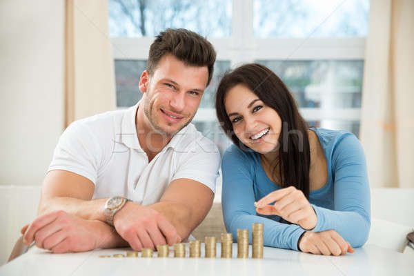 Happy Couple Arranging Stacks Of Golden Coins Stock photo © AndreyPopov