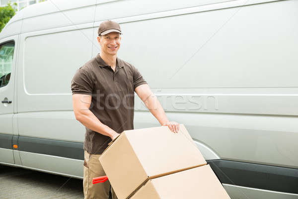 Delivery Man Holding Trolley With Cardboard Boxes Stock photo © AndreyPopov