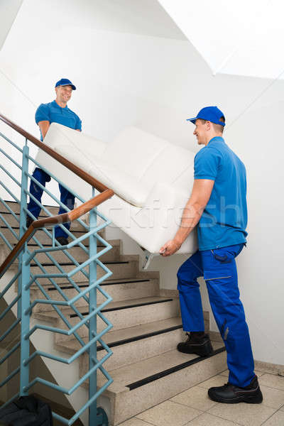 Two Male Movers Carrying Sofa On Staircase Stock photo © AndreyPopov