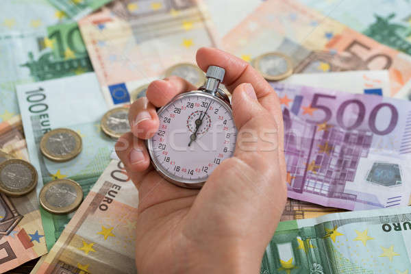 Person Hands With Stopwatch Over Money Stock photo © AndreyPopov