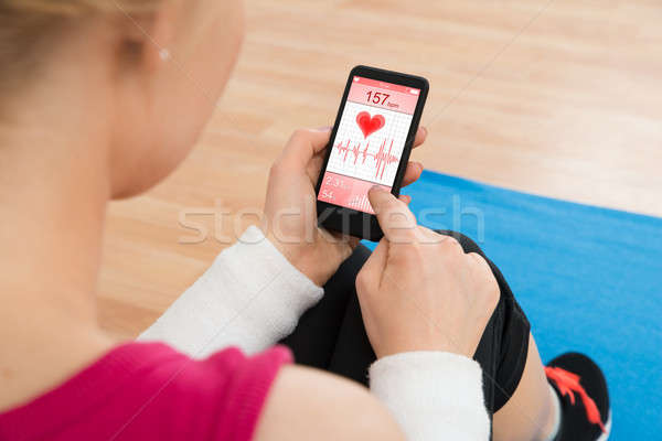 Woman With Mobile Phone Showing Pulse Rate Stock photo © AndreyPopov