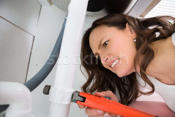 Woman With Monkey Wrench Tightening Pipe Stock photo © AndreyPopov